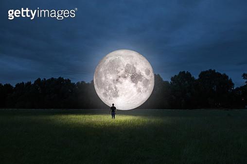 Man standing in front of moon - gettyimageskorea