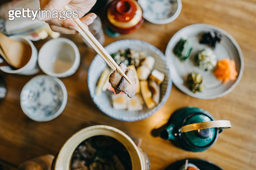 Overhead view of woman enjoying delicate Japanese cuisine with various side dishes and green tea in the restaurant - gettyimageskorea