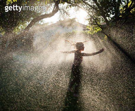 Young girl playing in sprinkler on hot summer day - gettyimageskorea