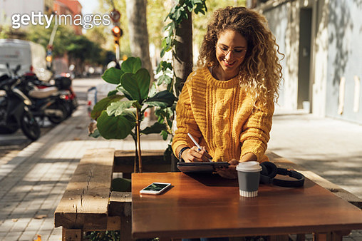 Smiling beautiful female student using digital tablet while sitting at sidewalk cafe in city - gettyimageskorea