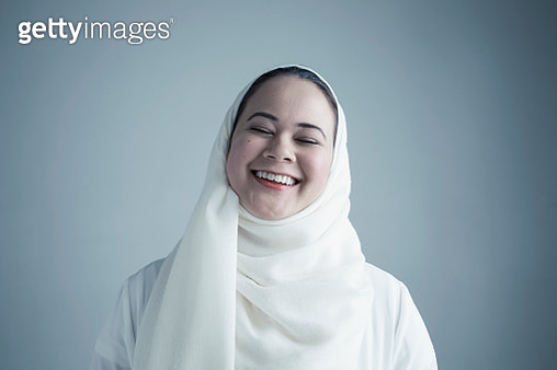 Portrait Middle Eastern young woman in white hijab laughing with eyes closed - gettyimageskorea