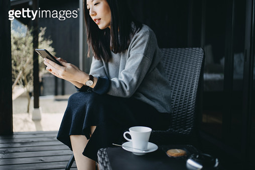 Beautiful young Asian woman using smartphone while relaxing with coffee and cookie at the balcony - gettyimageskorea