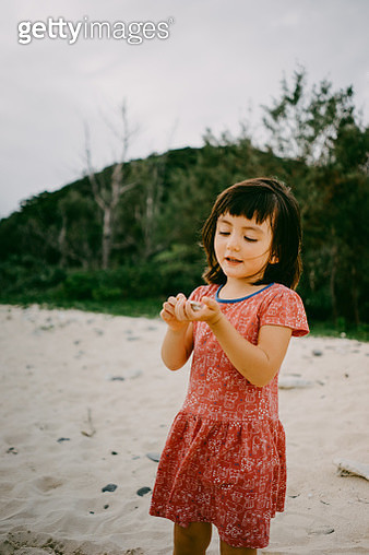 Cute mixed race girl holding seashells, Okinawa, Japan - gettyimageskorea