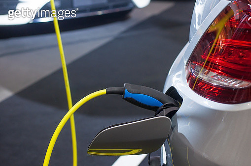 Close-Up Of Electric Car Being Charged On Street - gettyimageskorea
