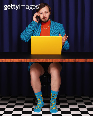 Man sitting at a desk with a laptop and talking on the phone with no trousers on. - gettyimageskorea