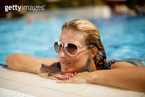 Beautiful woman relaxing in swimming pool - gettyimageskorea