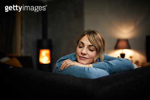 Portrait of woman relaxing on couch at home in the evening - gettyimageskorea