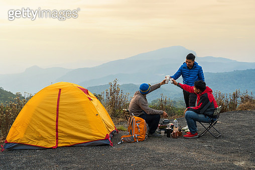 Group of asian people drinking and Clinking paper glasses of coffee beside tent comping in the deep forest over the scene of mountain landscape at the sunrise time, Traveler and camping concept - gettyimageskorea