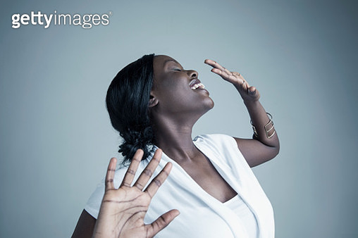 Portrait playful African American young woman smiling and dancing with eyes closed and head back - gettyimageskorea