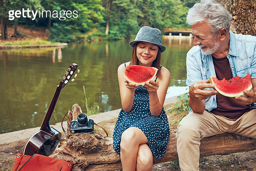 grandfather and granddaughter talking and eating watermelon on a nice day at the lake - gettyimageskorea