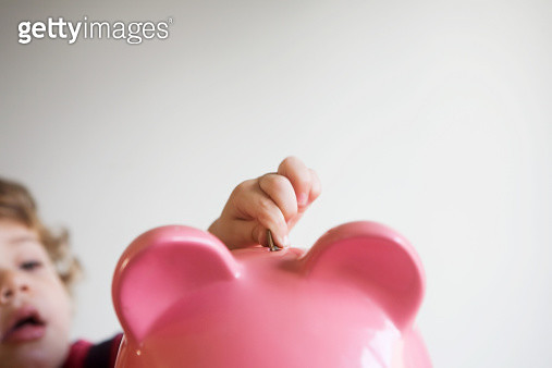 Little boy putting money in piggy bank - gettyimageskorea