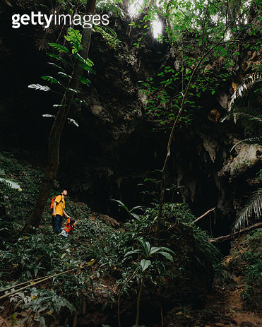Father and child exploring jungle cave, Iriomote-jima, Japan - gettyimageskorea
