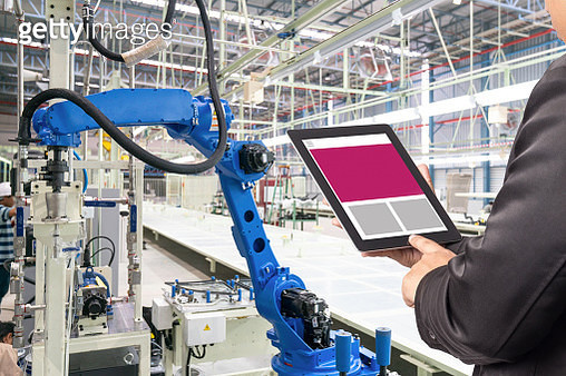 Engineer hand using tablet, heavy automation robot arm machine in smart factory industrial with tablet real time monitoring system application. Industry 4th iot concept. - gettyimageskorea