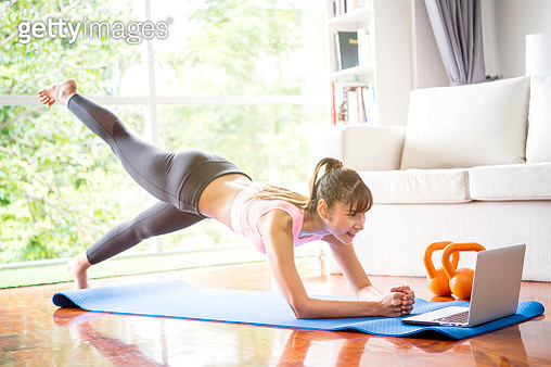 Healthy lifestyle and work life balance concepts. Young woman doing yoga excercise with online app on computer laptopn in her living room at home. - gettyimageskorea