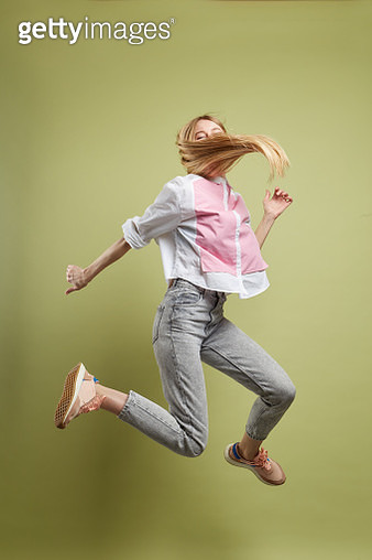 Young beautiful woman with long blond hair wearing white blouse and blue jeans jumping for joy and shaking her hair. Shot in studio on green background - gettyimageskorea
