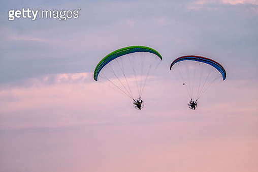 Person Paragliding Against Sky During Sunset - gettyimageskorea