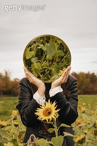 Close-Up Of Person Holding Mirror On Field - gettyimageskorea