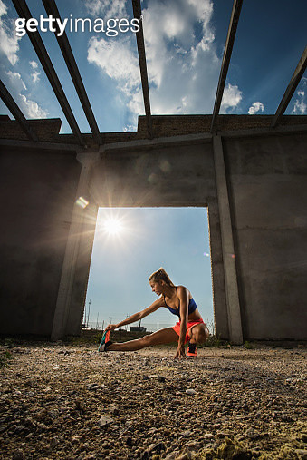 Female athlete stretching her leg before sports training on a sunny day. - gettyimageskorea