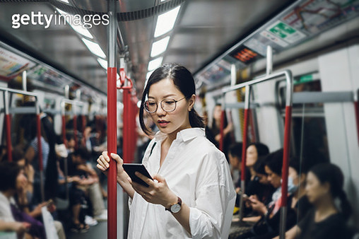 Young businesswoman looking at smartphone while riding on subway - gettyimageskorea