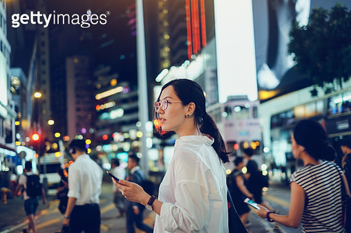 Beautiful Asian woman using mobile phone while crossing road in busy downtown city street at night - gettyimageskorea