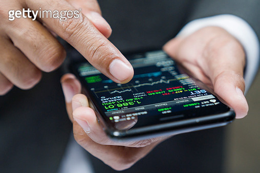 Woman buying cryptocurrency through mobile phone app - gettyimageskorea