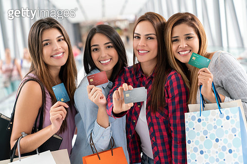Young female friends at the mall holding their credit cards while looking at camera smiling - gettyimageskorea