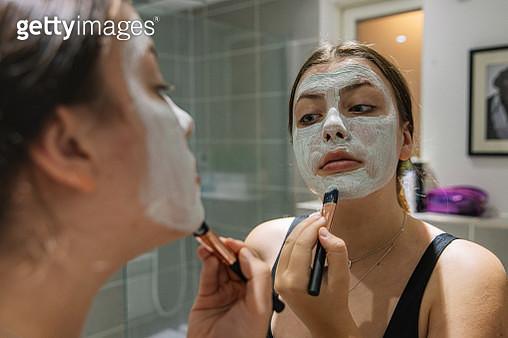 Teenage girl applying face mask in bathroom mirror - gettyimageskorea