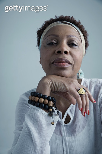 Portrait confident African American mature woman wearing headscarf and beaded bracelet - gettyimageskorea
