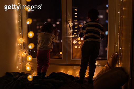 Brother and sister looking through window city lights at night - gettyimageskorea
