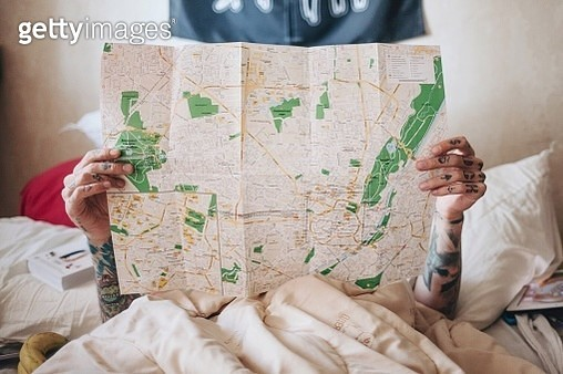 Woman Holding World Map While Lying On Bed At Home - gettyimageskorea