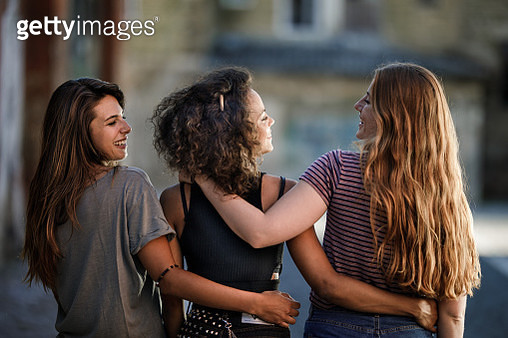Back view of embraced female friends on the street. - gettyimageskorea