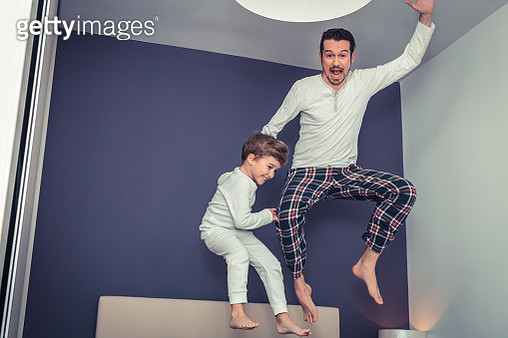 Playful Father And Son Jumping In Bedroom - gettyimageskorea