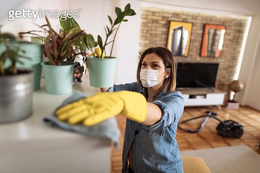 Woman wiping dust from shelf and other furniture in living room - gettyimageskorea