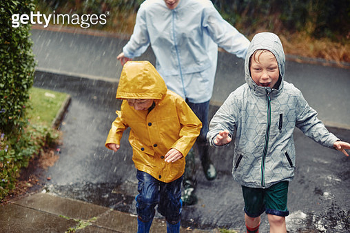 Family running home in the rain - gettyimageskorea