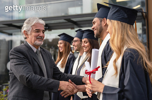 Teacher congratulating a group of students on graduation day - gettyimageskorea