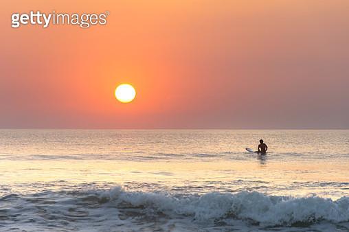 the surfer enjoying the sun set at kuta beach, bali - gettyimageskorea