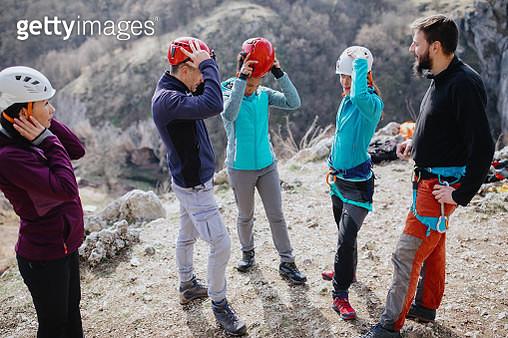 Rock climbers adjusting safety helmets - gettyimageskorea