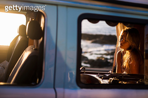 Spain, Tenerife, Blonde girl sitting in a van at sunset - gettyimageskorea