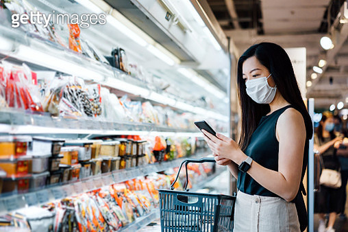 Young Asian woman with protective face mask holding shopping basket and using smartphone while grocery shopping in a supermarket - gettyimageskorea