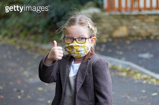 happy girl with thumb up wearing a face mask - gettyimageskorea
