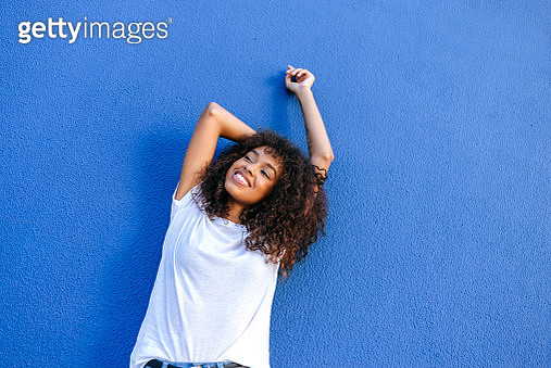 Portrait of smiling woman with blue background - gettyimageskorea