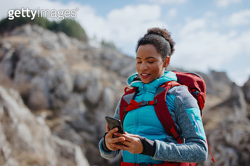 Woman taking photos of mountains in front of her - gettyimageskorea