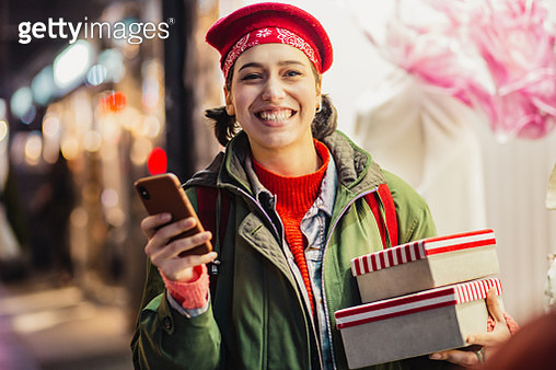 Young woman in a Christmas shopping using mobile phone - gettyimageskorea