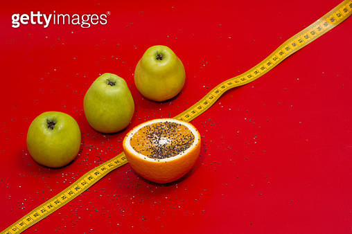 Close-Up Of Fruits And Tape Measure Over Red Background - gettyimageskorea