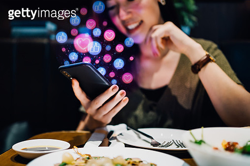 Smiling young Asian woman using smartphone on social media network application while having meal in the restaurant, viewing or giving likes, love, comment, friends and pages. Social media addiction concept - gettyimageskorea