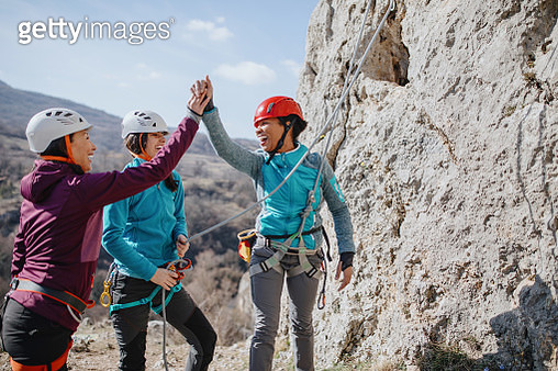 Climbers giving high fives after successfully finishing climb - gettyimageskorea