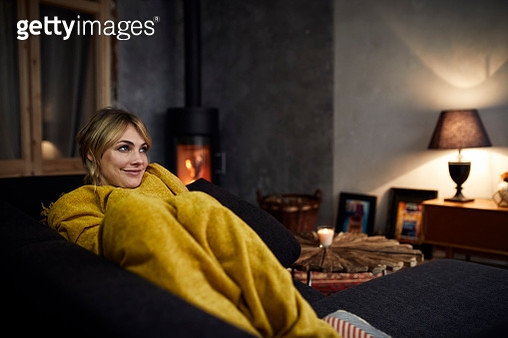 Portrait of smiling woman relaxing on couch at home in the evening - gettyimageskorea