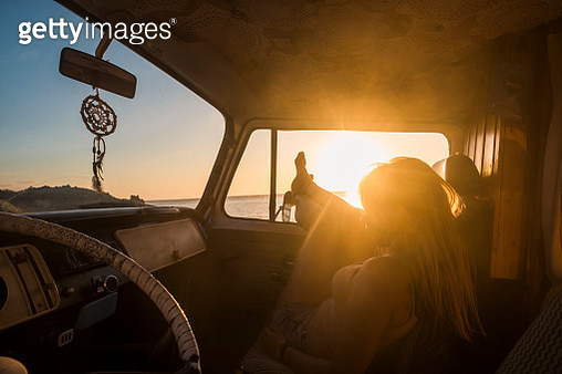 Spain, Tenerife, young woman lying in a van at sunset - gettyimageskorea