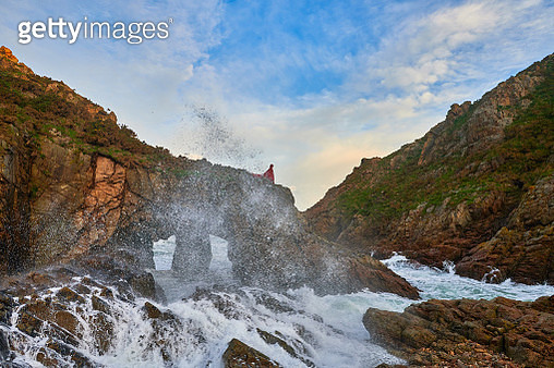 Woman walking on the edge of water on the cliff with wearing red coat, feeling mysterious - gettyimageskorea