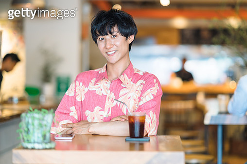 A portrait of a modern man while drinking iced coffee in cafe. - gettyimageskorea